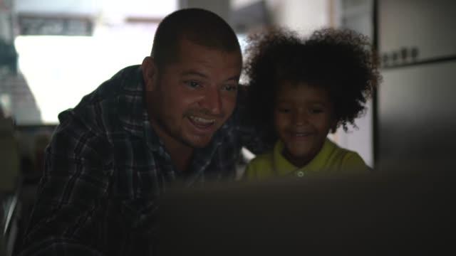 vídeos de stock, filmes e b-roll de pai e filho fazendo uma videoconferência no laptop em casa - 40 44 anos