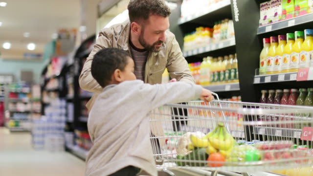 vidéos et rushes de father and son doing weekly shop in grocery store - denrée périssable