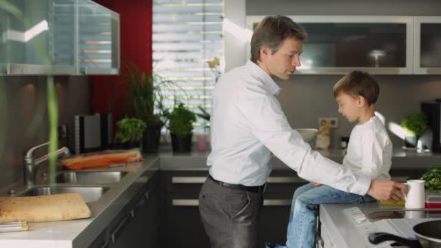 MS Father and son (4-5) eating cornflakes in kitchen / Kleinmachnow, Brandenburg, Germany