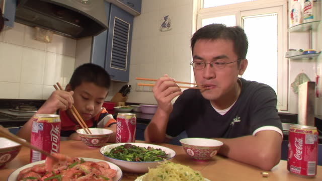 CU, Father and son (12-13) eating shrimps at kitchen table, Shanghai, China