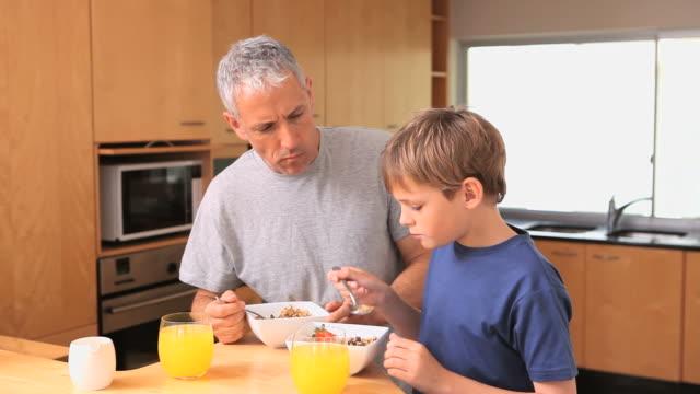 vídeos de stock e filmes b-roll de father and son eating their breakfast - cabelo branco