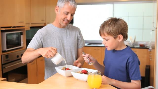 vídeos de stock e filmes b-roll de father and son eating their breakfast together - cabelo branco