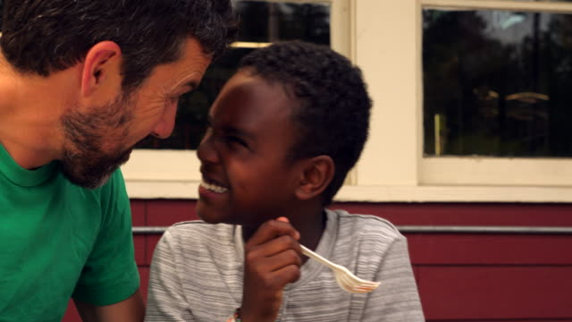 ms father and son embracing and laughing while having lunch at picnic table outside grocery store - happiness stock videos & royalty-free footage