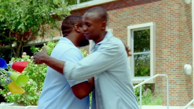vidéos et rushes de ms, father and son embracing outside college dorm building, san antonio, texas, usa - fils de