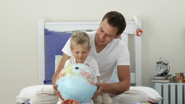 stockvideo's en b-roll-footage met ms father and son (4-5) examining globe, sitting on bed / cape town, western cape, south africa - bureauglobe
