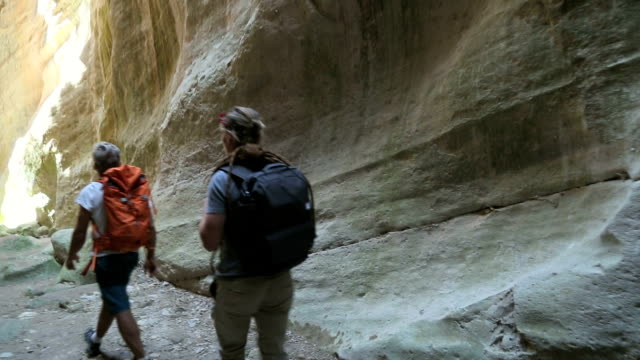father and son explore slot canyon - slot canyon stock videos and b-roll footage