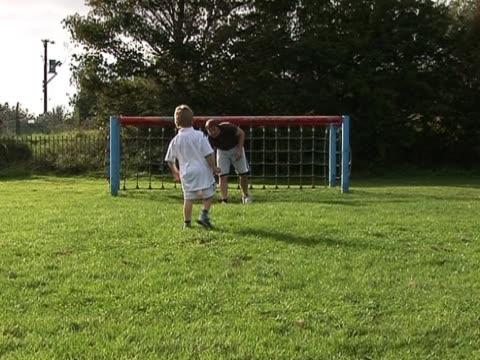 vídeos y material grabado en eventos de stock de padre e hijo de familia jugando fútbol o fútbol americano - marcar términos deportivos