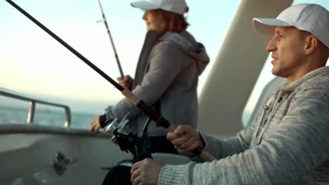 vídeos y material grabado en eventos de stock de hd: padre e hijo pesca desde la stern - barco pesquero