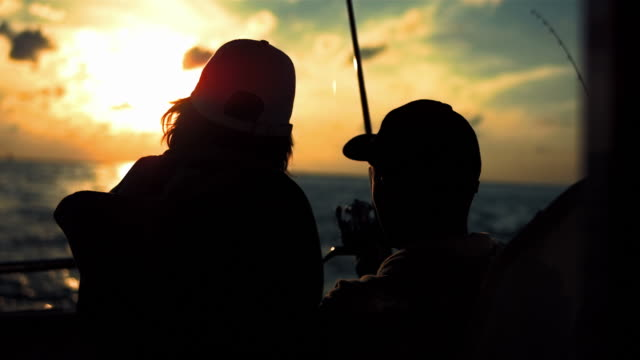 hd: father and son fishing on the boat at sunset - nautical vessel stock videos & royalty-free footage