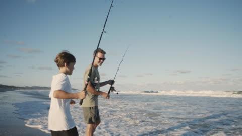vídeos de stock, filmes e b-roll de pai e filho juntos de pesca na praia - pescaria