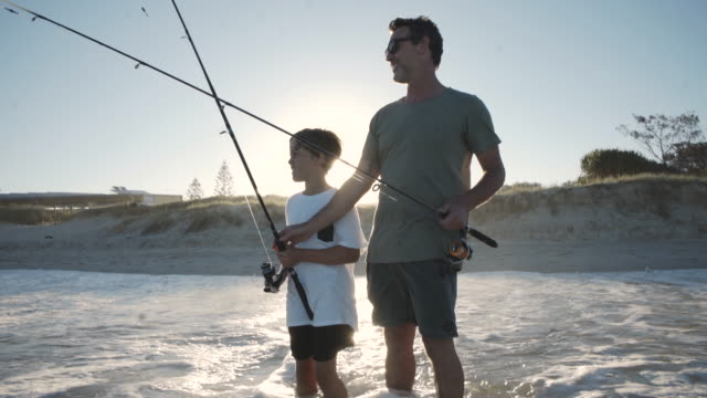 father and son fishing together at the beach - fisher role stock videos & royalty-free footage
