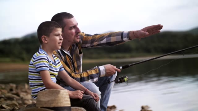 father and son fishing together. - explaining stock videos & royalty-free footage