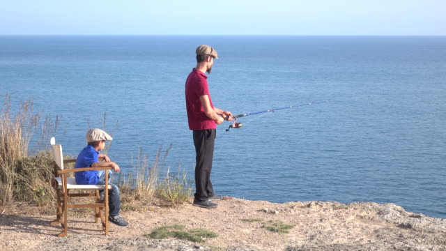 vater und sohn beim angeln - schiebermütze stock-videos und b-roll-filmmaterial