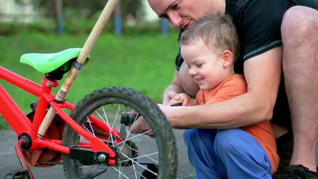 father and son fixing bicycle tire - stabilisers stock videos & royalty-free footage