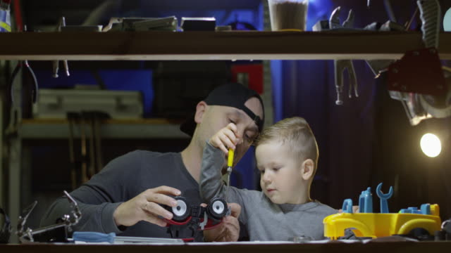 father and son fixing together a toy tractor with screwdriver in garage and little boy is learning to work with tools shot on red camera - leksak bildbanksvideor och videomaterial från bakom kulisserna