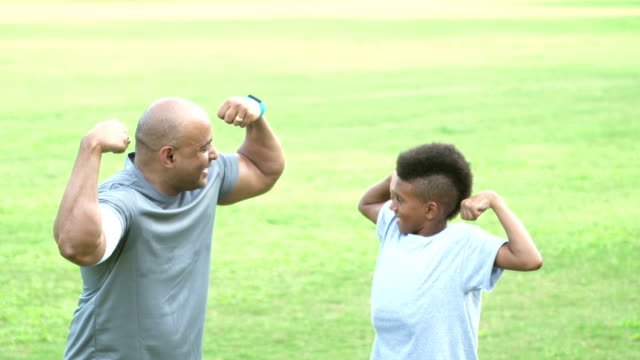 father and son flexing muscles - strength stock videos & royalty-free footage