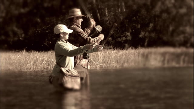 MS SELECTIVE FOCUS Father and son (12-13) fly fishing in river, sepia toned / Tampa, Florida, USA