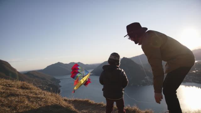 padre e figlio volano aquilone sulla cima della montagna al tramonto - scoperta video stock e b–roll
