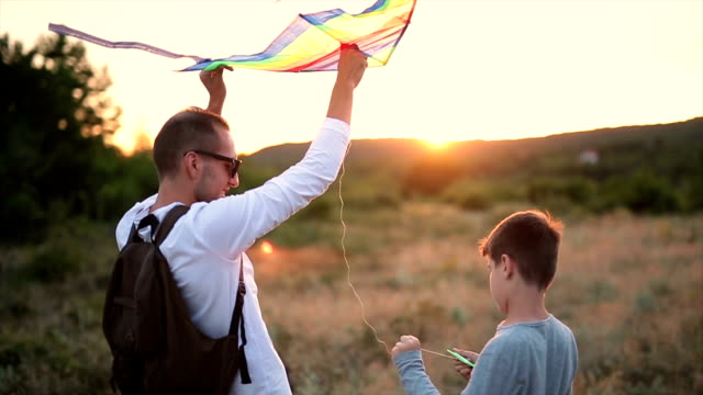 father and son flying kites - kite toy stock videos and b-roll footage