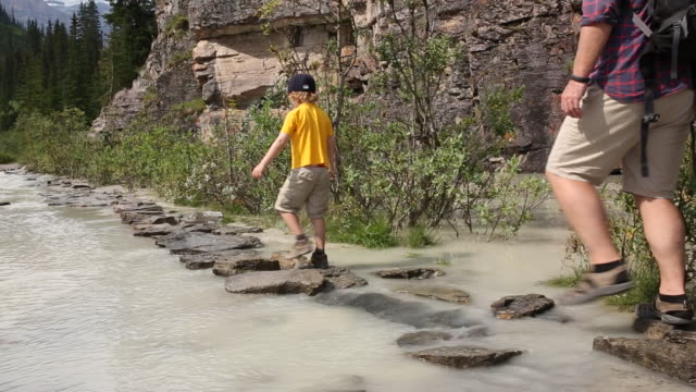 father and son follow stepping stones along creek - stepping stone stock videos & royalty-free footage