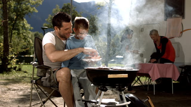 hd dolly: father and son grilling meat on barbecue - camping stock videos & royalty-free footage