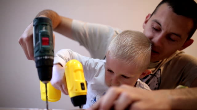 father and son have fun while he drilling - art and craft stock videos & royalty-free footage