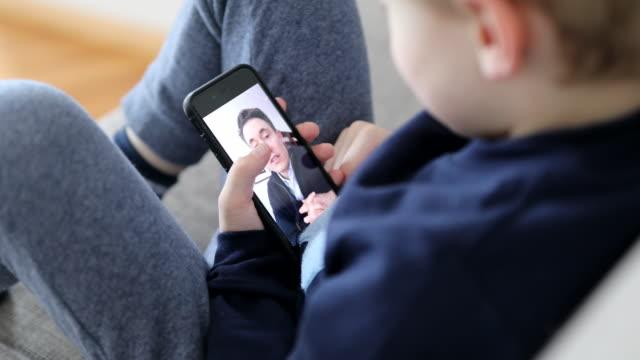 vídeos de stock, filmes e b-roll de pai e filho tendo uma chamada de vídeo durante a quarentena de bloqueio covid-19 - filme imagem em movimento