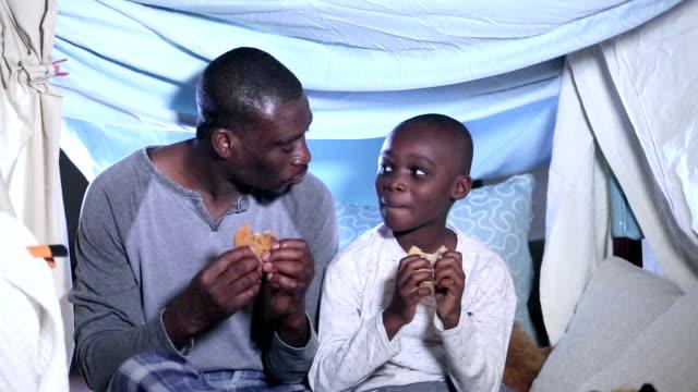 padre e figlio che bevano uno spuntino prima di coricarsi sotto una tenda fatta in casa - 30 39 years video stock e b–roll