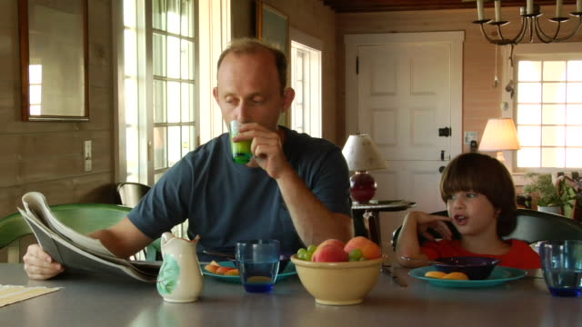 ms, father and son (6-7) having breakfast in cottage, north truro, massachusetts, usa - balding stock videos & royalty-free footage