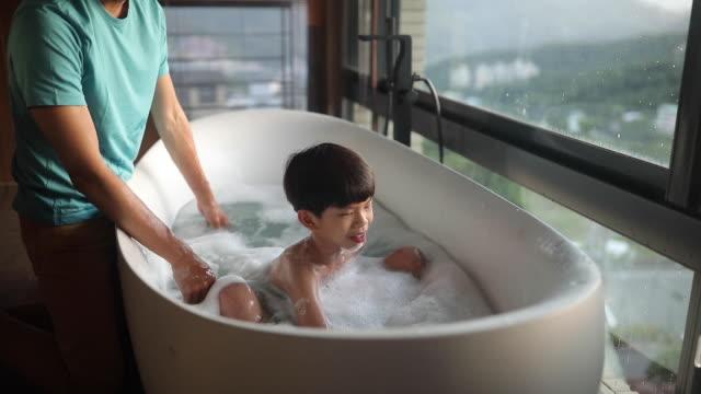 vídeos de stock e filmes b-roll de father and son having fun during bathing time - menino infancia pelado banheiro