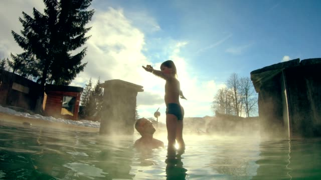 father and son having fun in geothermal pool - steam stock videos & royalty-free footage