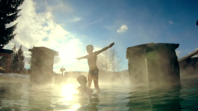 father and son having fun in geothermal pool - hot spring stock videos & royalty-free footage