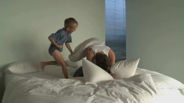 ws father and son (6-7) having pillow fight on bed / cape town south africa - 枕投げ点の映像素材/bロール