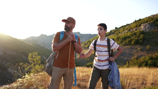 father and son hiking together in mountains - recreational pursuit stock videos & royalty-free footage