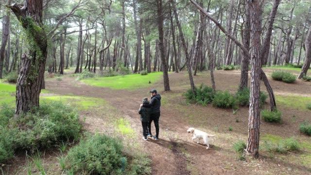 Far och son vandra med träpinne i skogen