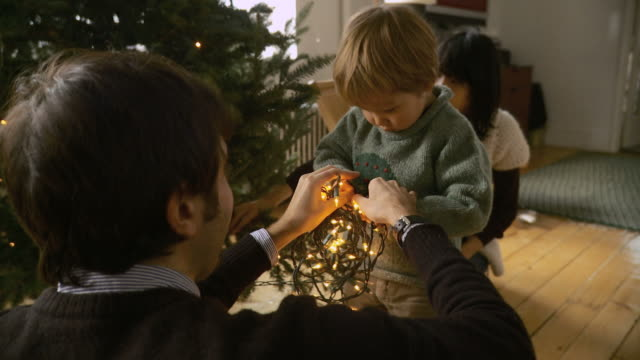 stockvideo's en b-roll-footage met ms father and son (2-3) holding fairy lights for decorate christmas tree / new york city, new york, usa  - kerstboom versieren