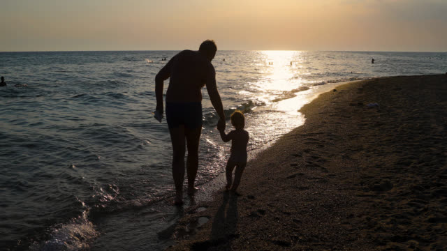 father and son holding hands and walking on the beach during beautiful sunset - mediterranean sea stock videos & royalty-free footage