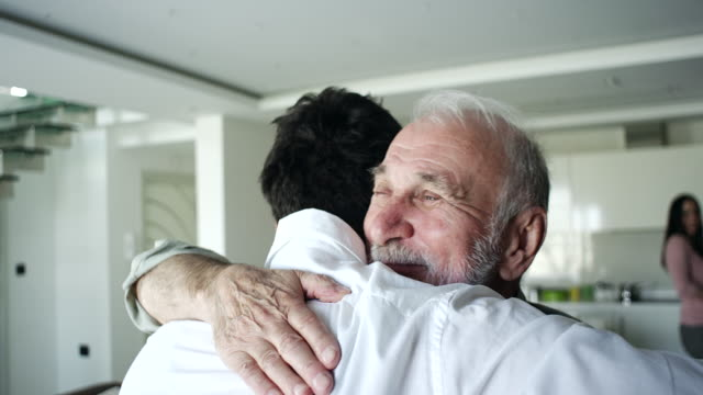 father and son hugging in living room - stringere tenere video stock e b–roll