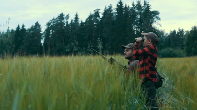 vídeos de stock e filmes b-roll de father and son hunting for boar (slow motion) - espingarda