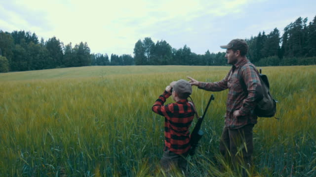 father and son hunting for boar - gun stock videos & royalty-free footage
