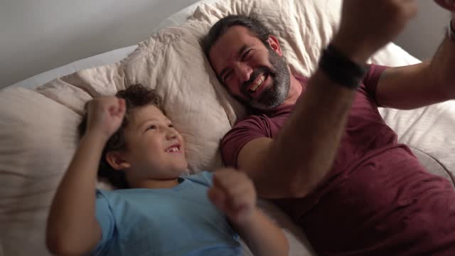 father and son in bed playing pretending to be driving - genderblend stock videos & royalty-free footage