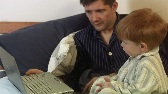Father and son in bed with a laptop, Sweden.