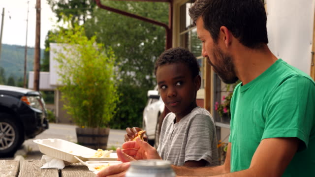 ms father and son in discussion while sharing lunch at outdoor cafe - genderblend stock videos & royalty-free footage