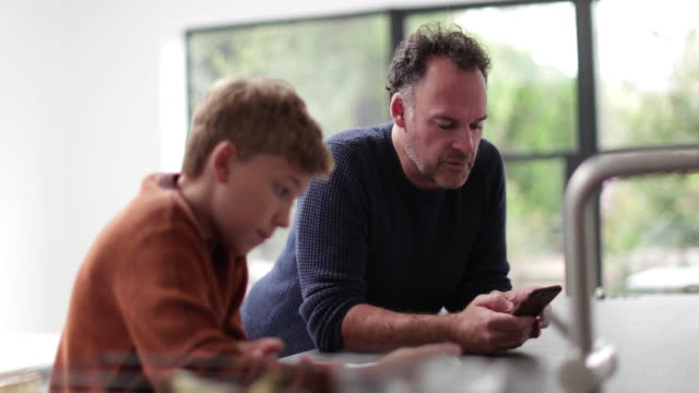 Father and Son in kitchen looking at smartphone