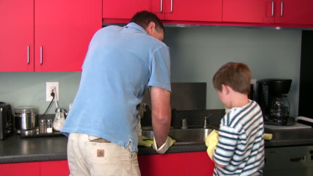 (hd1080i) father and son in kitchen - glove stock videos and b-roll footage