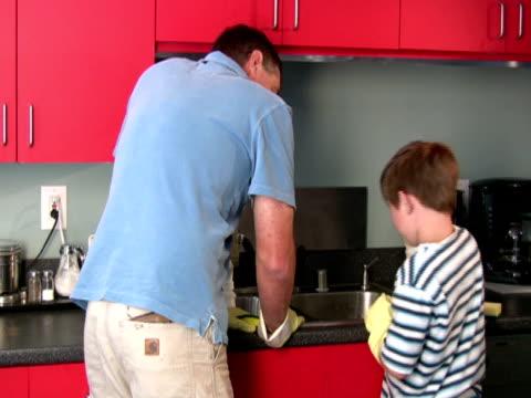 vídeos de stock, filmes e b-roll de pai e filho na cozinha - luva roupa de proteção