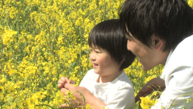 Father and son in rapeseed field