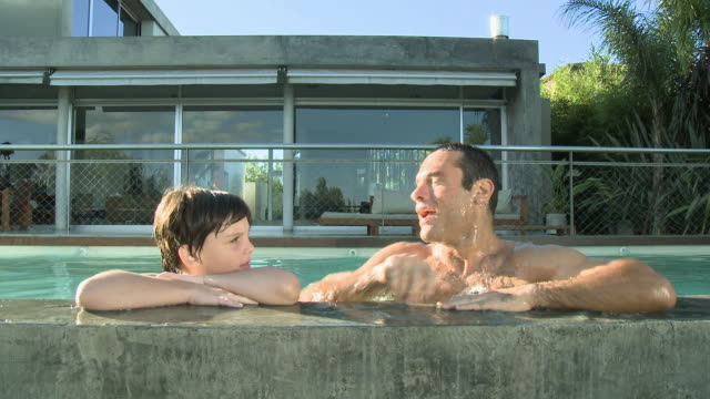 Father and son in swimming pool, smiling at camera