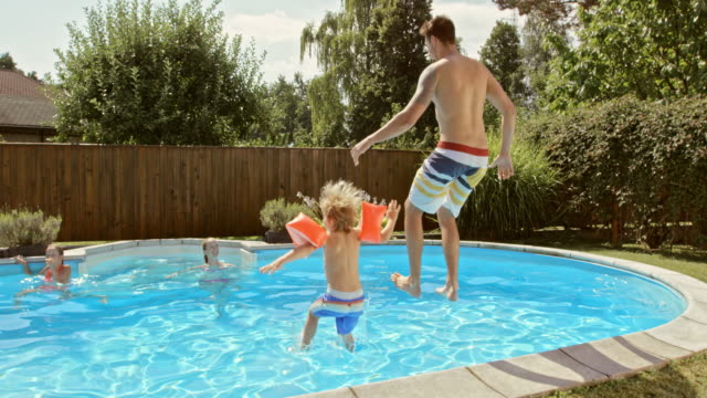 slo mo cs father and son jumping into the pool together - front or back yard stock videos & royalty-free footage