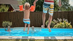 SLO MO DS Father and son jumping into the pool